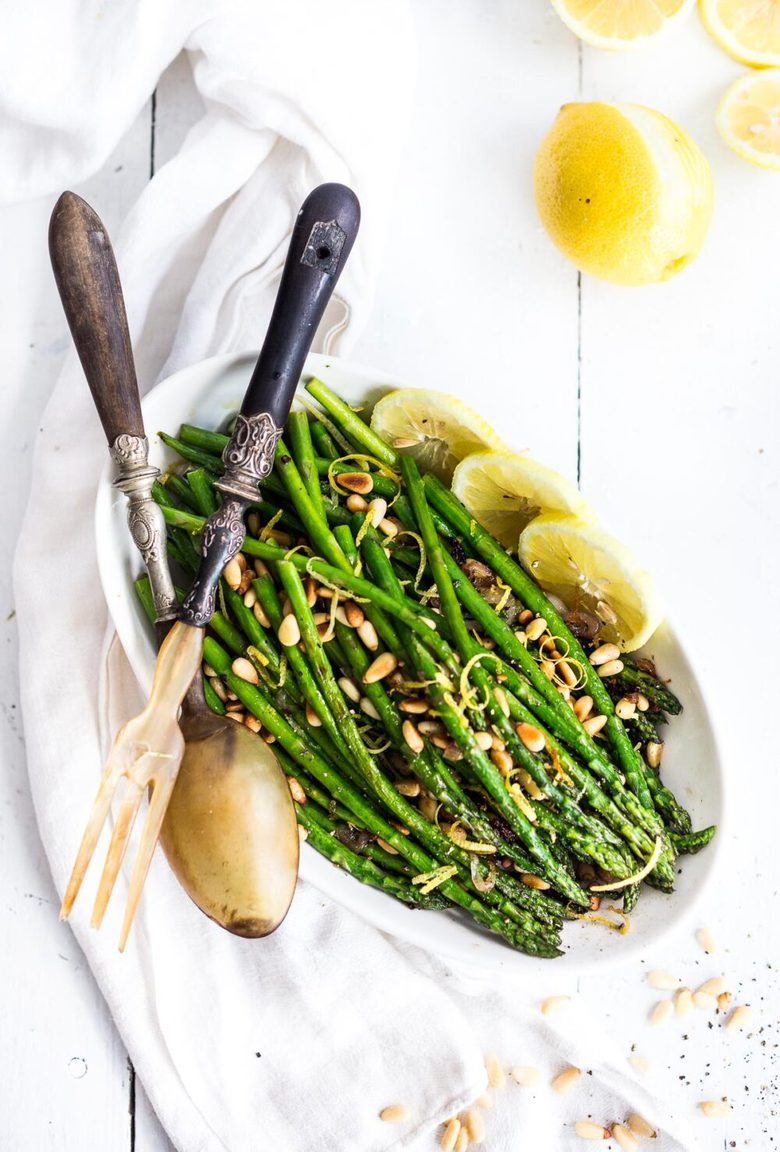 Simple Roasted Asparagus baked in the oven with lemon, garlic and olive oil. Can be made in 20 minutes! An easy vegan side dish, perfect for spring. #roastedasparagus