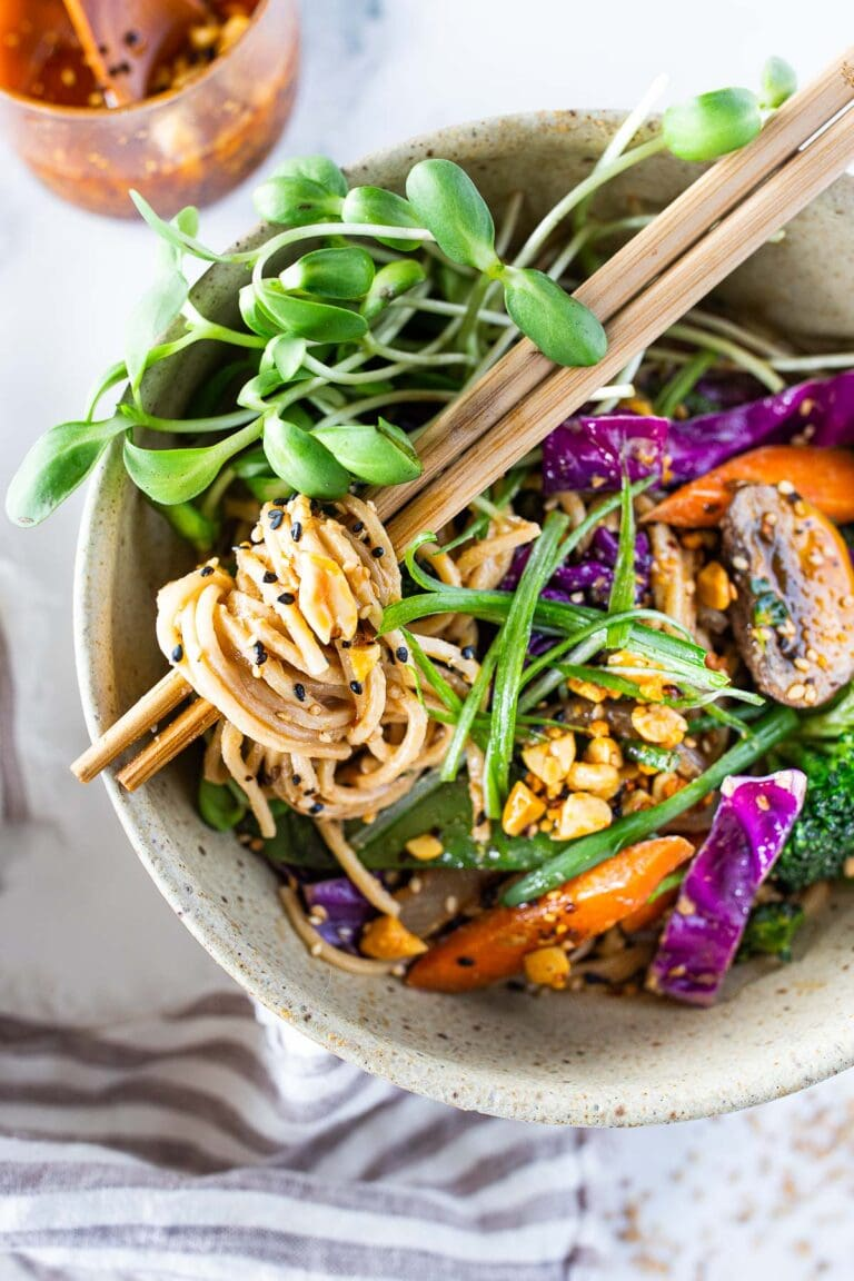 Flavorful Sesame Noodles, loaded up with healthy veggies and tossed in the most delicious, creamy, vegan Sesame Sauce! Make this in 20 minutes flat! Keep it vegan or add chicken- up to you! #sesamenoodles #vegan #noodlebowl