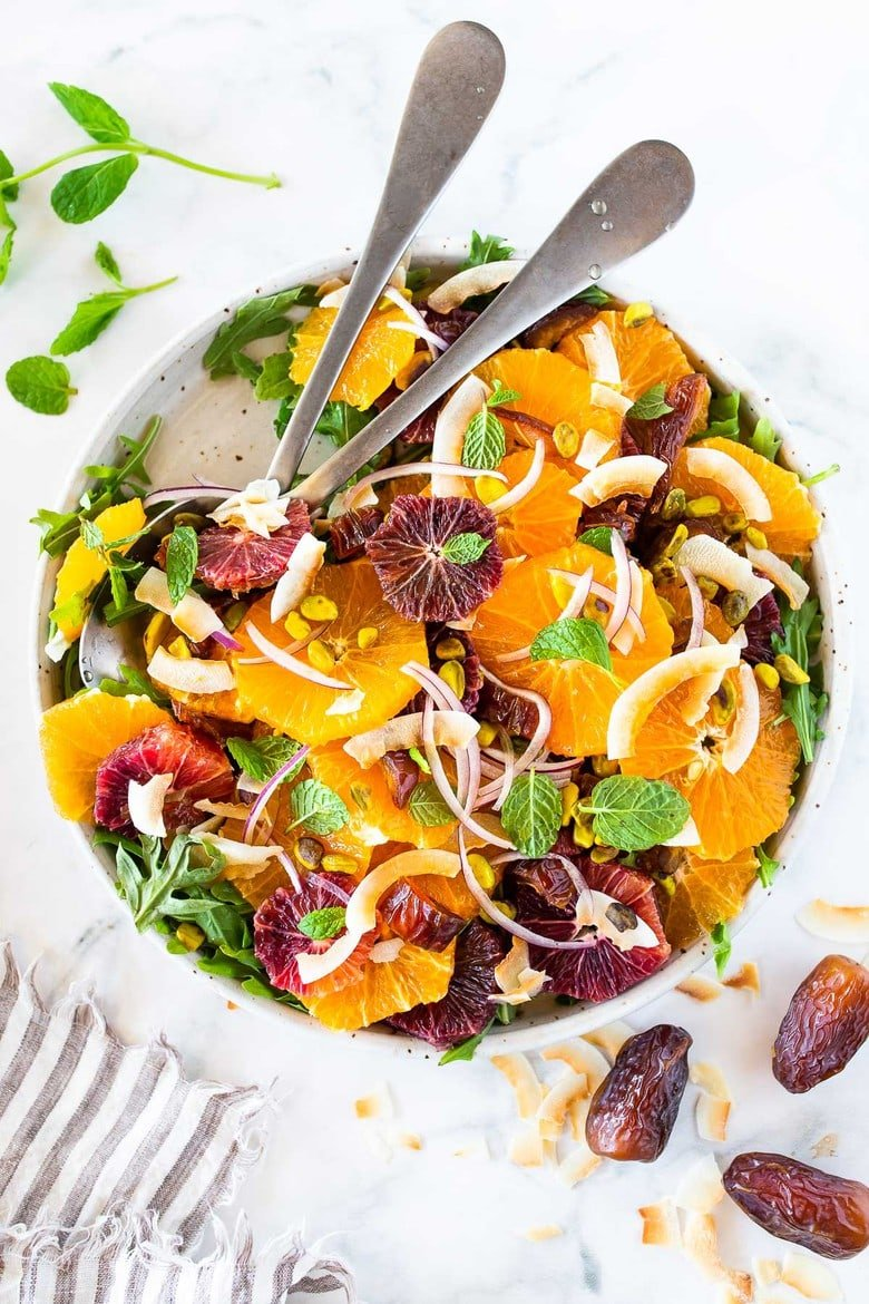 This Moroccan-inspired Orange Salad with dates, arugula, mint, pistachios, and toasted coconut is dressed in the most flavorful Citrus Shallot Vinaigrette. It's deliciously juicy and vegan! #citrussalad #orangesalad