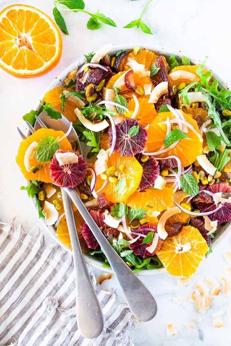 This Moroccan-inspired Citrus Salad with dates, arugula, mint, pistachios, and toasted coconut is dressed in the most flavorful Citrus Shallot Vinaigrette. It's deliciously juicy and vegan!#citrussalad #orangesalad