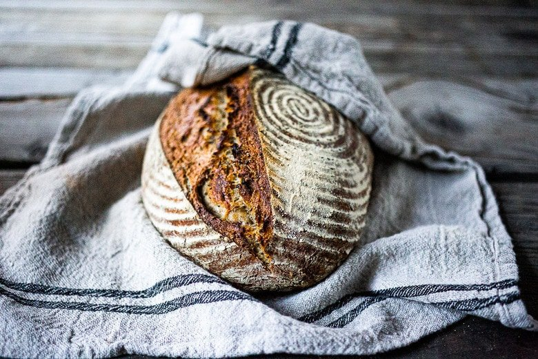 A simple EASY recipe for No-Knead Sourdough Bread that takes very little hands-on time, rising overnight and bakes in the morning.