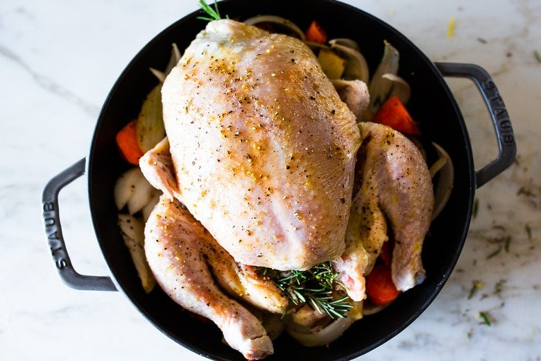 A simple easy recipe for roast chicken with lemon, garlic and rosemary, baked in the oven over vegetables. A delicious dinner recipe that can be turned into other meals during the week!