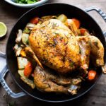 How to roast a WHOLE CHICKEN! Easy Roast Chicken with lemon, garlic and rosemary, baked in the oven over vegetables. A delicious dinner recipe! #roastchicken