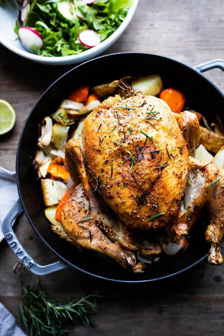 A simple easy recipe for roast chicken with lemon, garlic and rosemary, baked in the oven over vegetables. A delicious dinner recipe! #roastchicken