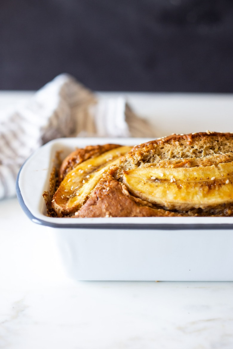This Banana bread is not only healthy and vegan, but it can also be made with sourdough starter or discard! Infused with ginger, spices and crusted with sesame seeds it is flavorful and moist. #bananabread #veganbananabread #sourdough #yeastless
