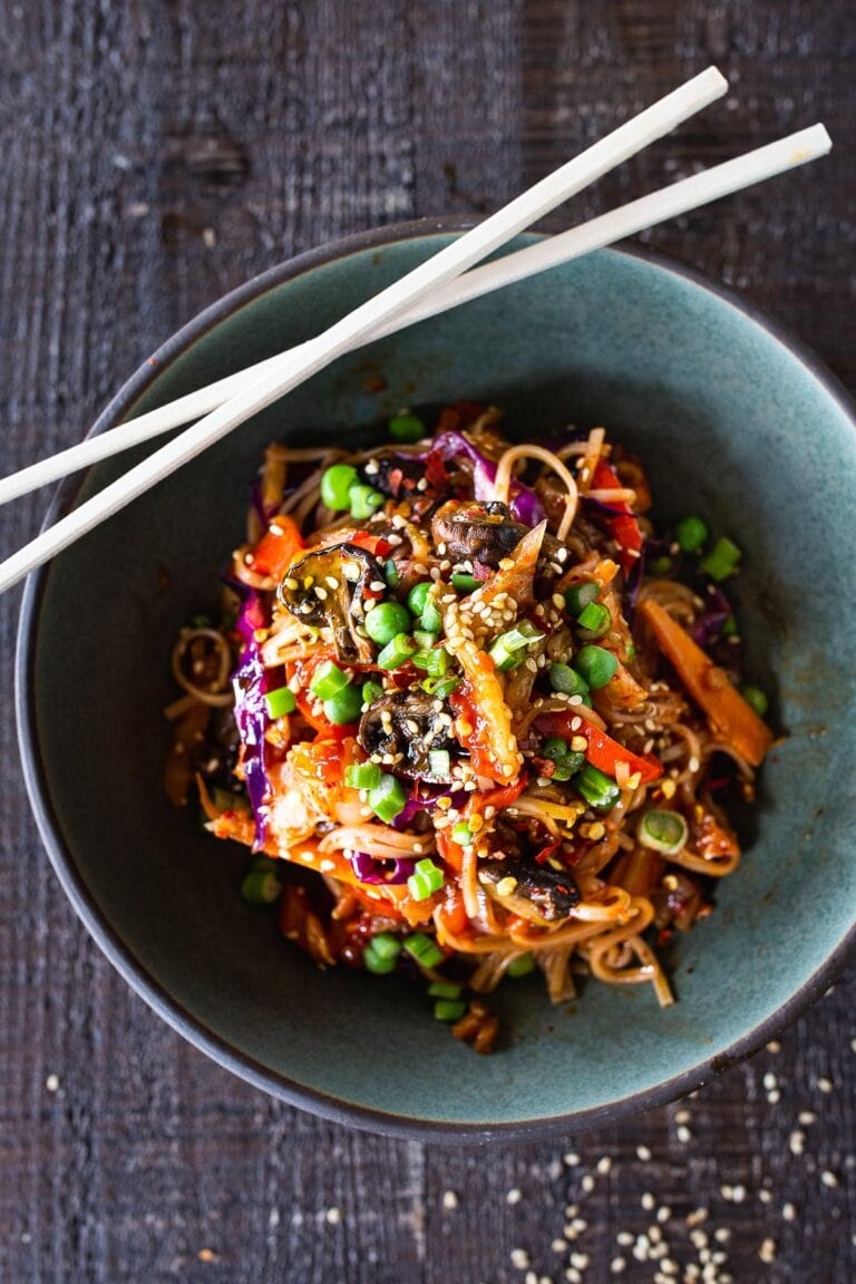 Here's a super tasty recipe for Vegan Kimchi Noodles, stir-fried with lots of healthy veggies you probably have on hand. Keep it vegan or add an egg, chicken or shrimp! Crispy tofu is also a delicious option here!#kimchi #kimchinoodles #kimchirecipes #vegannoodles