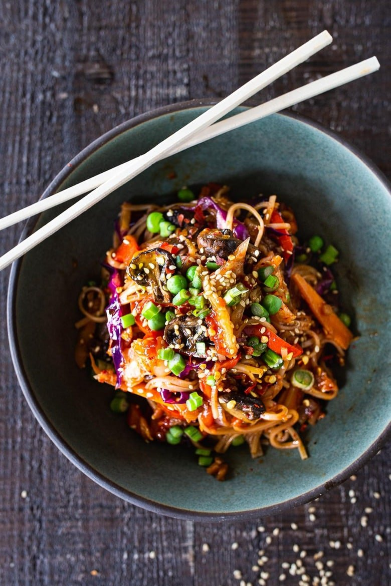 Here's a super tasty recipe for Vegan Kimchi Noodles, stir-fried with lots of healthy veggies you probably have on hand. Keep it vegan or add an egg, chicken or shrimp! Crispy tofu is also a delicious option here! #kimchi #kimchinoodles #kimchirecipes #vegannoodles