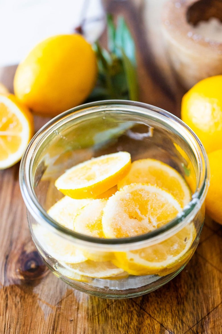 How to Preserve Lemons- a simple easy way to preserve lemons that only takes 10 minutes of hands-on time before letting mother nature take its course. Use in dressings, marinades, Middle Eastern Dishes and salad to add a burst of flavor. #preservedlemons