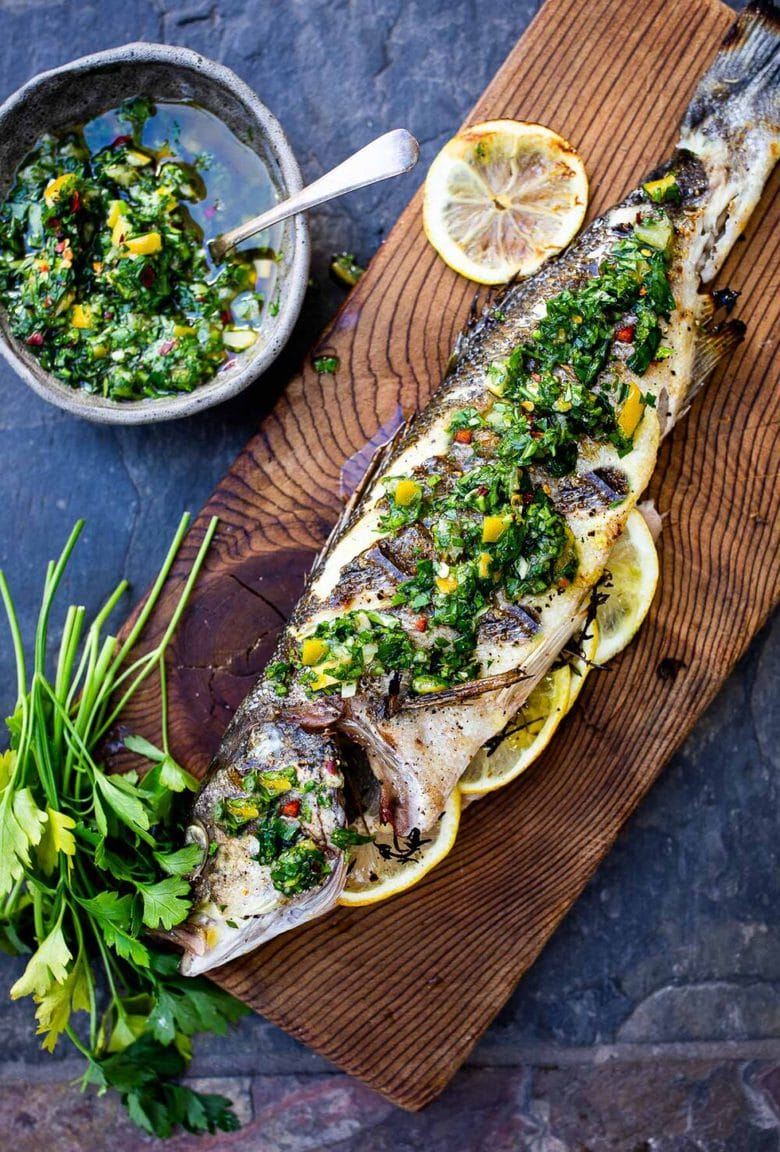 How to grill a whole fish (Branzino) topped with the most flavorful Preserved Lemon Gremolata, (Zesty Herb Sauce) in about 30 minutes flat! A simple easy Mediterranean dinner! #branzino #grilledfish #wholefish #grilledbranzino