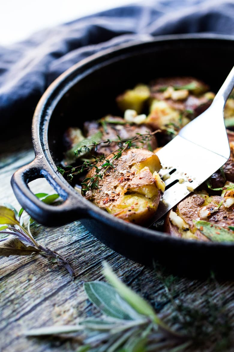 Crispy Smashed Potatoes with Garlic and Herbs- a healthy vegan side perfect for breakfast or dinner! #veganside #potoatoes #smashedpotatoes #veganpotatoes