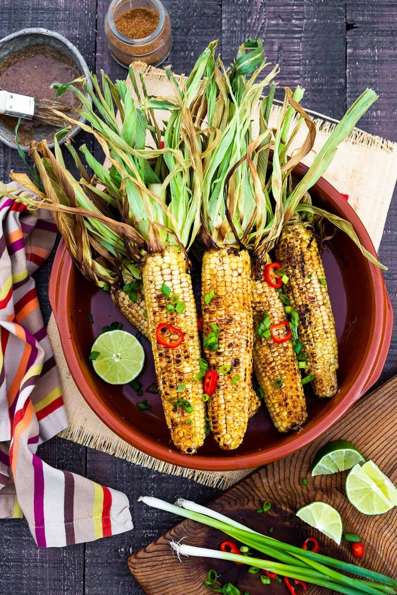 This flavorful Masala Street Corn hails from the streets of Mumbai! It's grilled and brushed with a mixture of ghee and garam masala spice! A squeeze of lime adds a delicious brightness. A tasty summer side dish to add to your next Indian feast! #grilledcorn #masalacorn #indiancorn #streetcorn