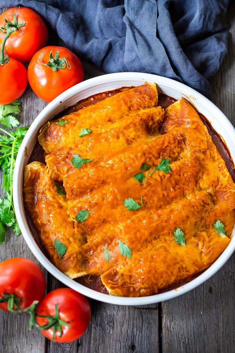 Chicken Enchiladas made with the BEST Enchilada Sauce (easy red sauce) and shredded chicken. A delicious comfort food meal the whole family will love. #enchiladas #chickenenchiladas
