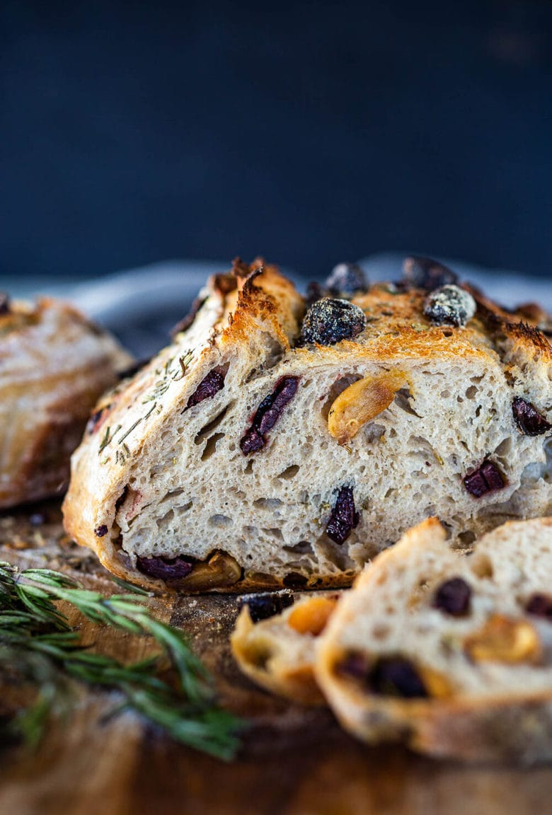 How to make Crusty Sourdough Bread, infused with rosemary, roasted garlic and olives that requires no kneading and rises overnight.Made with sourdough starter instead of yeast! #sourdoughbread