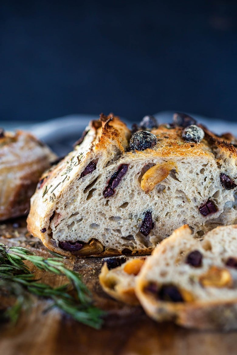 How to make Crusty Sourdough Bread, infused with rosemary, roasted garlic and olives that requires no kneading and rises overnight. Made with sourdough starter instead of yeast! #sourdoughbread