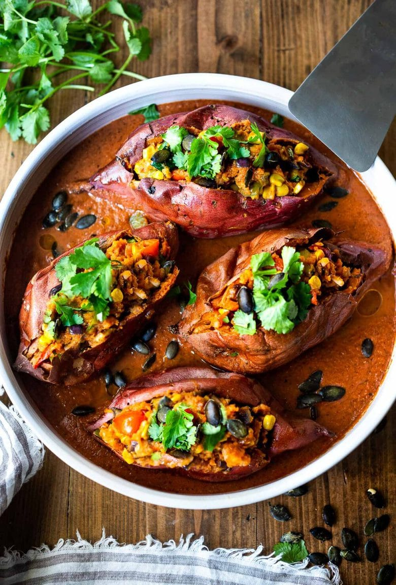 Baked Sweet Potatoes are loaded up with healthy veggies and infused with Oaxacan flavors, served over optional Mole Sauce. Vegan, flavorful and perfect for Sunday meal prep. #bakedsweetpotatoes #sweetpotatoes #vegandinner #mealprep #veganrecipe