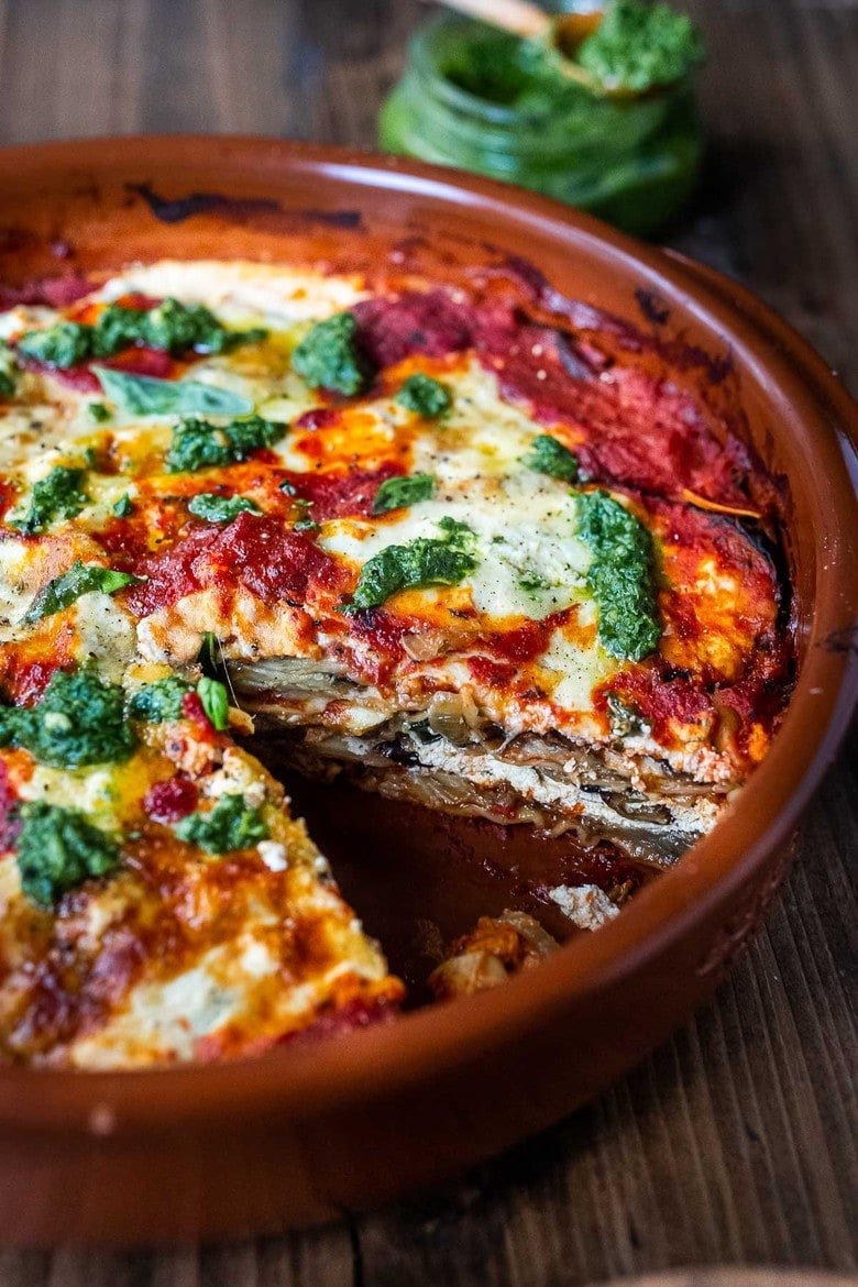 Eggplant Lasagna made with no-boil noodles and topped with Arugula Pesto. A delicious, healthy vegetarian dinner recipe that is comforting and nourishing. #eggplantlasagna