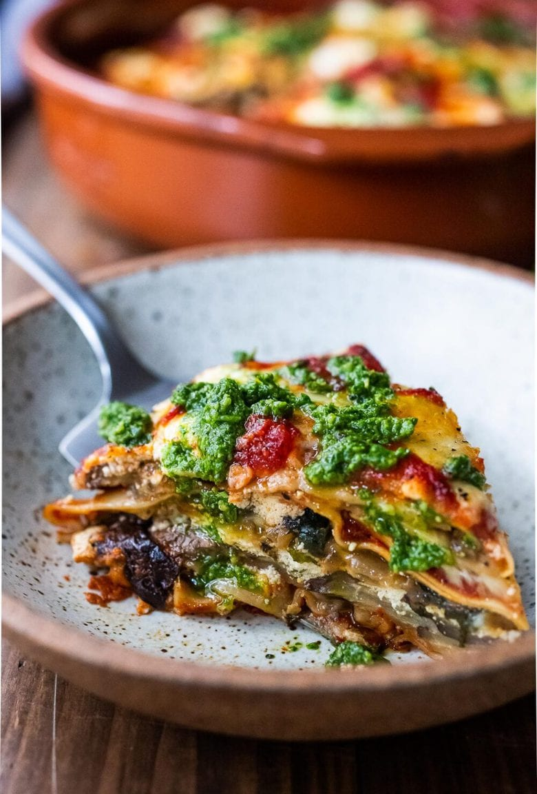 Eggplant Lasagna made with no-boil noodles and topped with Arugula Pesto. A delicious, healthy vegetarian dinner recipe that is comforting and nourishing. #vegetarian #eggplantlasagna #lasagna #healthycomefortfood