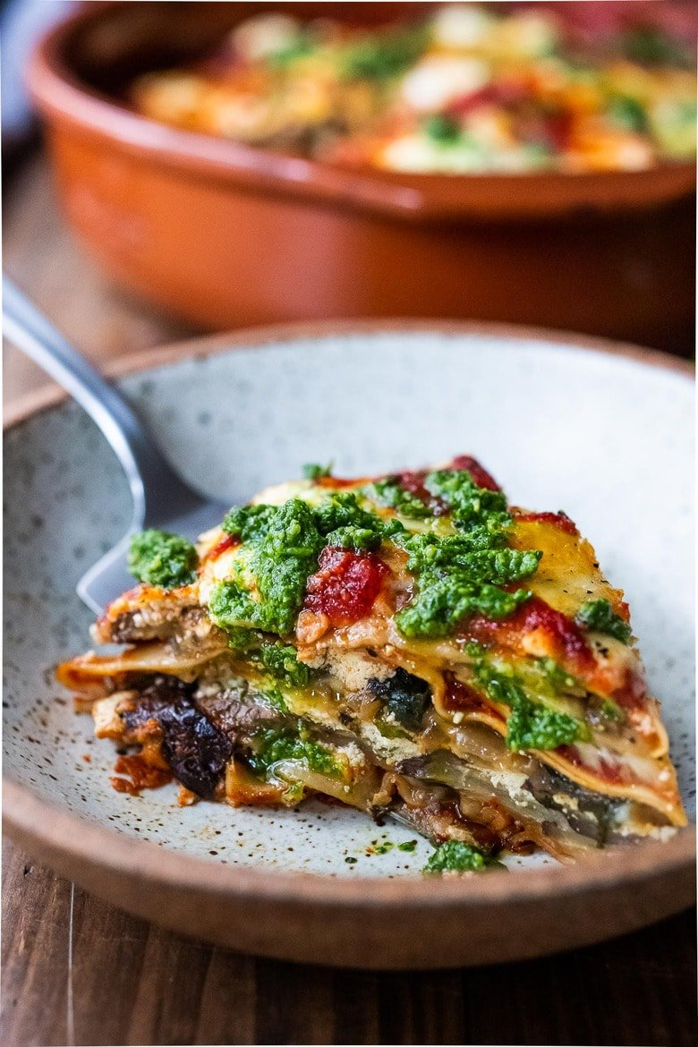 Easy Eggplant Lasagna made with no-boil noodles and topped with Arugula Pesto. A delicious, healthy vegetarian dinner recipe that is comforting and nourishing. #vegetarian #eggplantlasagna #lasagna #healthycomefortfood