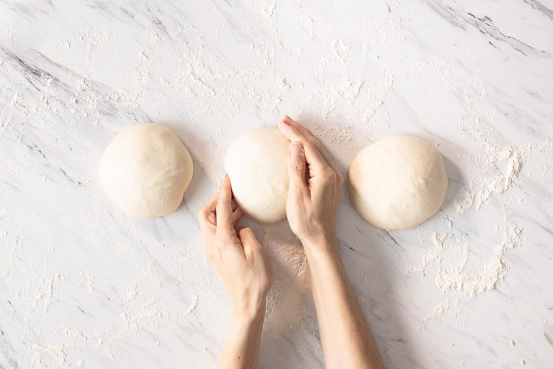 Using a circular cupping motion with the palm of your hand, gently roll each ball of dough on the countertop to create a taut ball.
