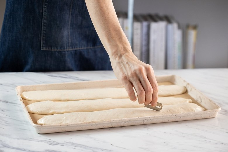 Using a lame (or sharp knife or razor blade), make 3-5 diagonal slashes into each piece of dough.