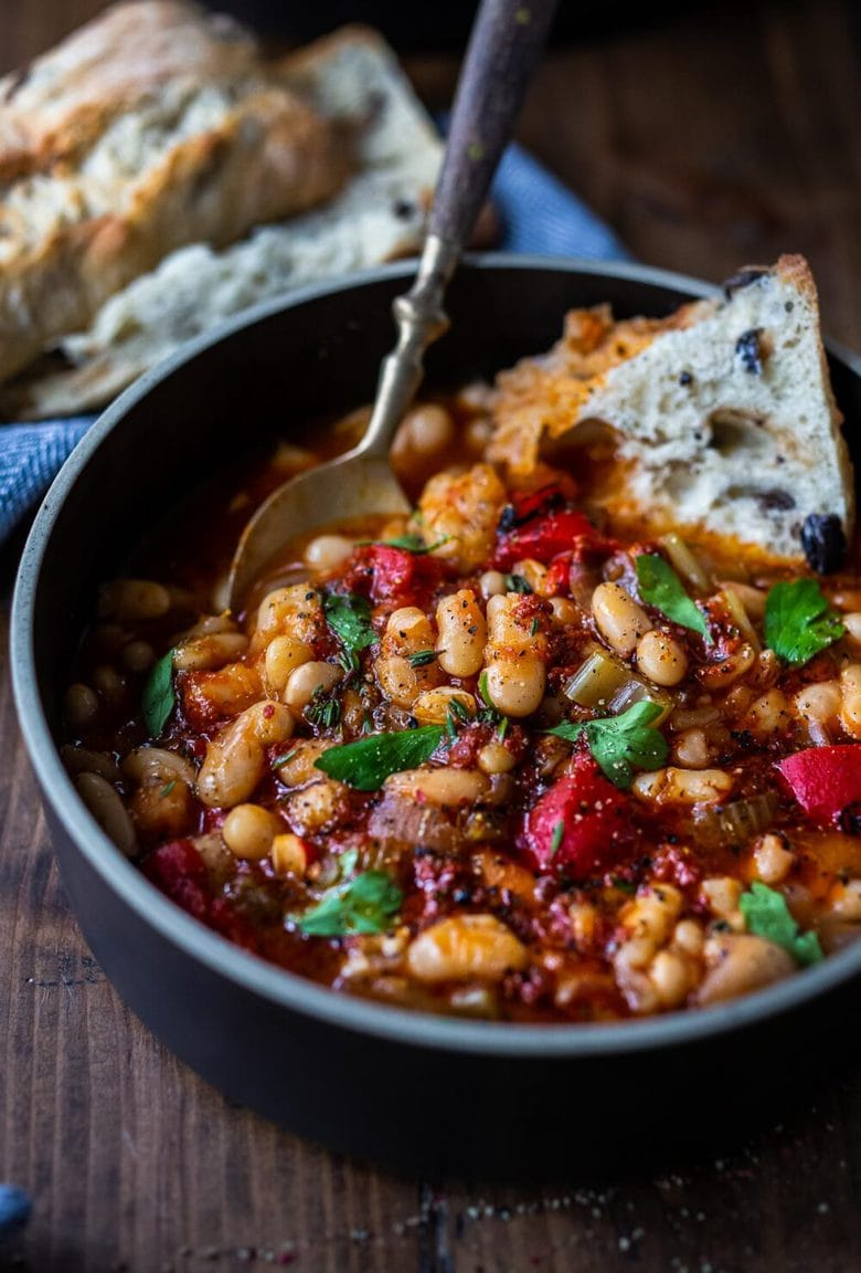 Here's a simple, hearty White Bean Soup you can make in your Instant Pot or on the stovetop using dry beans. Smoked paprika and optional Harissa paste give it a delicious flavor that will have you coming back for seconds.  Low in calories, high in fiber, this soup is vegan and gluten-free. #whitebeansoup