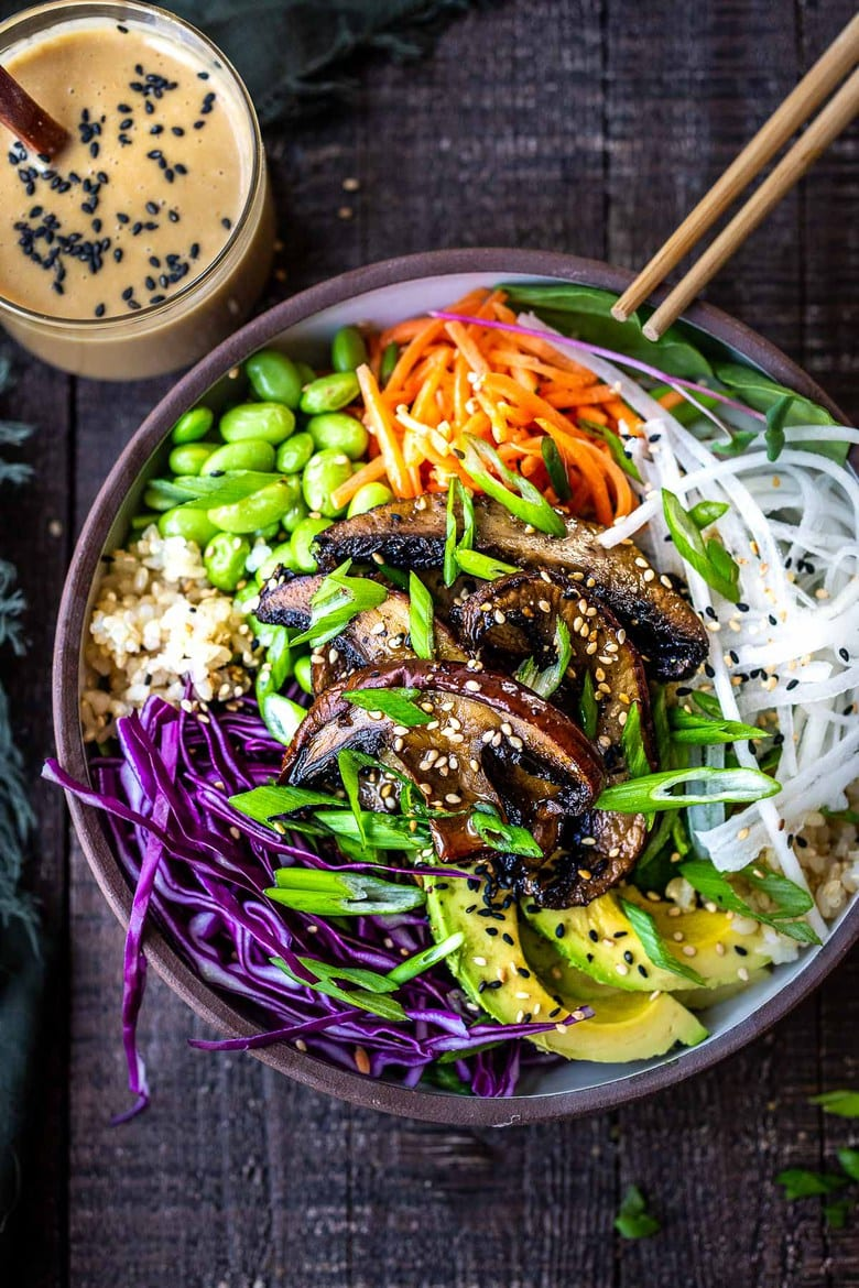 A flavorful Miso Mushroom Bowl with brown rice, avocado, cabbage, carrots, daikon, edamame and a Miso Ginger Dressing. Vegan and Gluten free. #bowl #veganbowl #vegandinner #mushroombowl