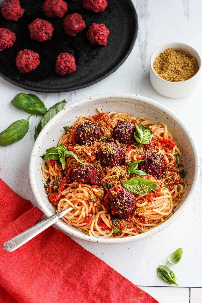 Vegan Spaghetti and Beetballs!  A beautiful twist on the comforting familiar classic.  Beets, black beans, walnuts and basil make these plant-based meatballs scrumptious and so satisfying.  Top with an easy rustic tomato sauce for a meal the whole family will love! #vegan #veganmeatballs #beetballs #spaghetti #veganspaghetti