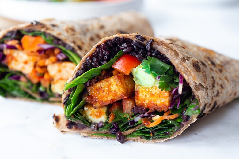 Scrumptious Thai Burrito with Peanut Sauce, baked peanut Tofu, black rice, spicy sriracha black beans and shredded crunchy veggies all wrapped up in a warm, whole wheat tortilla. #vegan #veganburrito #thaiburrito