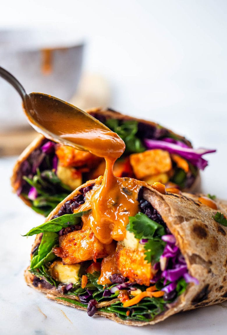 Thai Burrito with Peanut Sauce, baked peanut Tofu, black rice, spicy sriracha black beans and shredded crunchy veggies all wrapped up in a warm, whole wheat tortilla. #vegan #veganburrito #thaiburrito