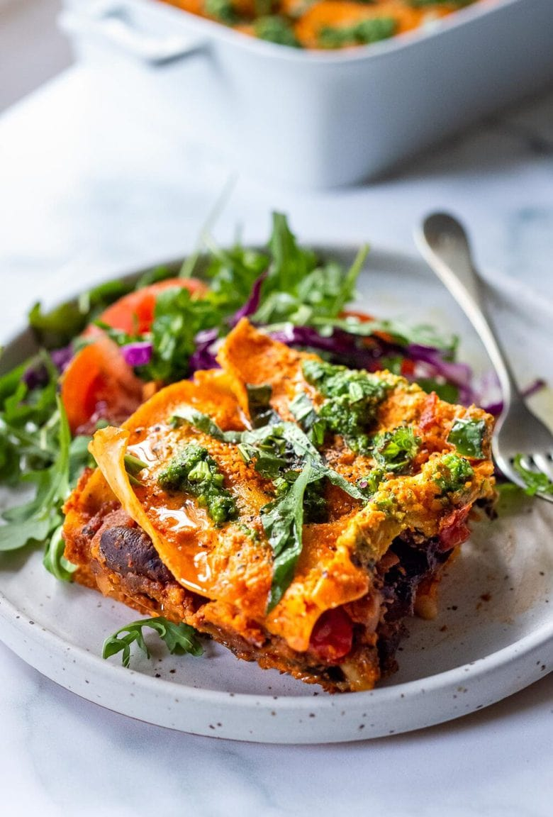 This Vegan Lasagna is made with a robust mushroom-spinach bolognese sauce, fresh basil, vegan ricotta and no-boil lasagna noodles, topped off with a creamy marinara sauce, drizzled with Arugula Basil Pesto. Vegan comfort food at its best! #veganlasagna #vegandinnerrecipes #vegan #lasagna #mushroombolognese