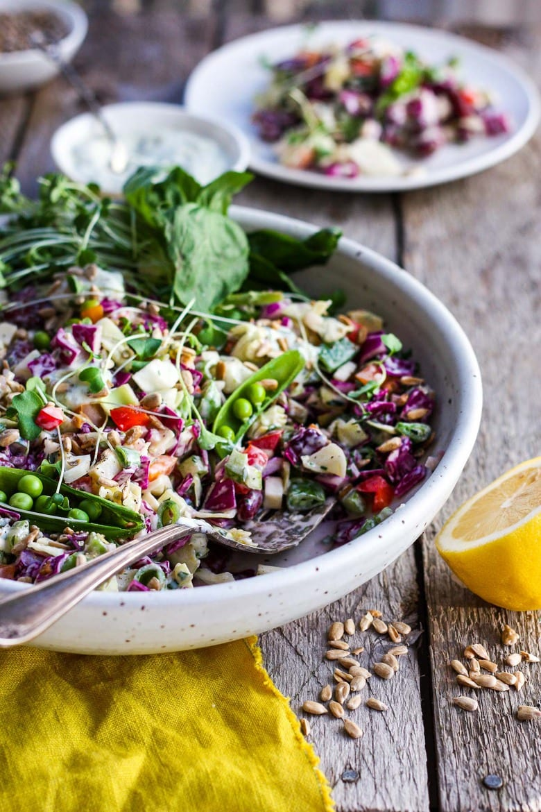 This Rainbow Chopped Salad is crunchy, colorful and nutritious! Tossed with a lemony herbed greek yogurt dressing, it is easy to make and easy to adapt. Perfect for meal prep, this salad keeps for 4 days in the fridge. #choppedsalad #yogurtdressing