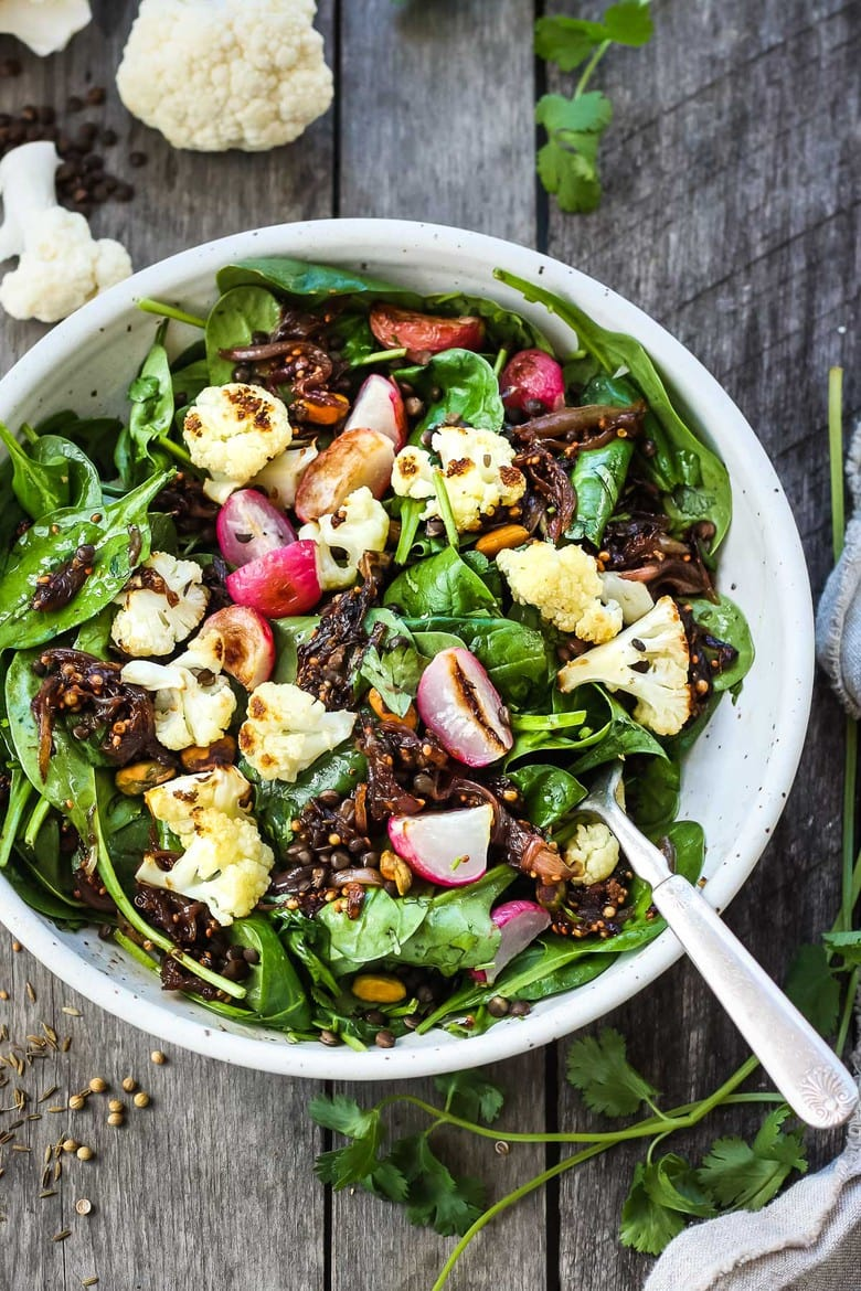 Afresh and flavorful Indian Spinach Salad with black lentils,roasted cauliflower and roasted radishes. Caramelized shallots and a Tempered Seed Dressing give the salad amazing flavor, depth and crunchy texture. #spinachsalad #indiansalad #vegan