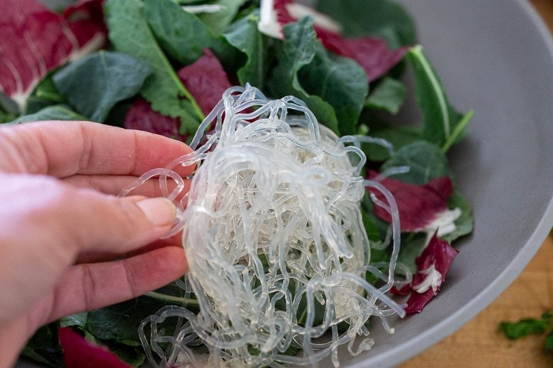 layering the salad with kelp noodles