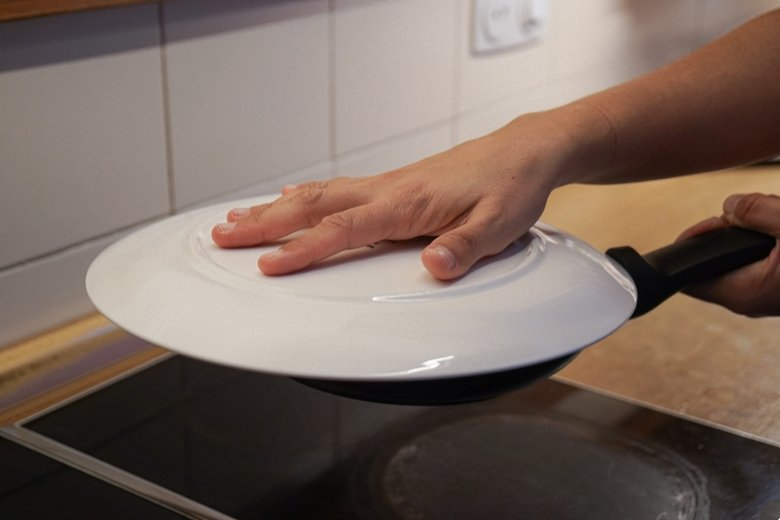 Flip the tortilla placing a plate over the skillet