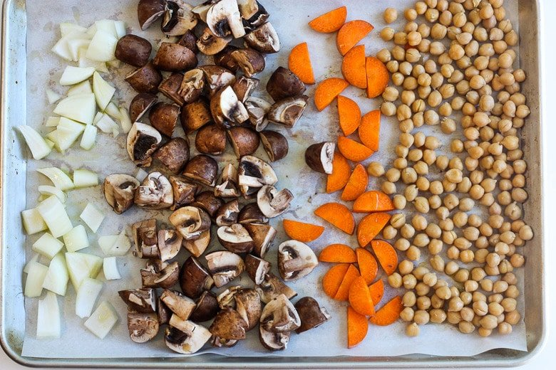 mushrooms, onions, carrots and chickpeas on a roasting pan.