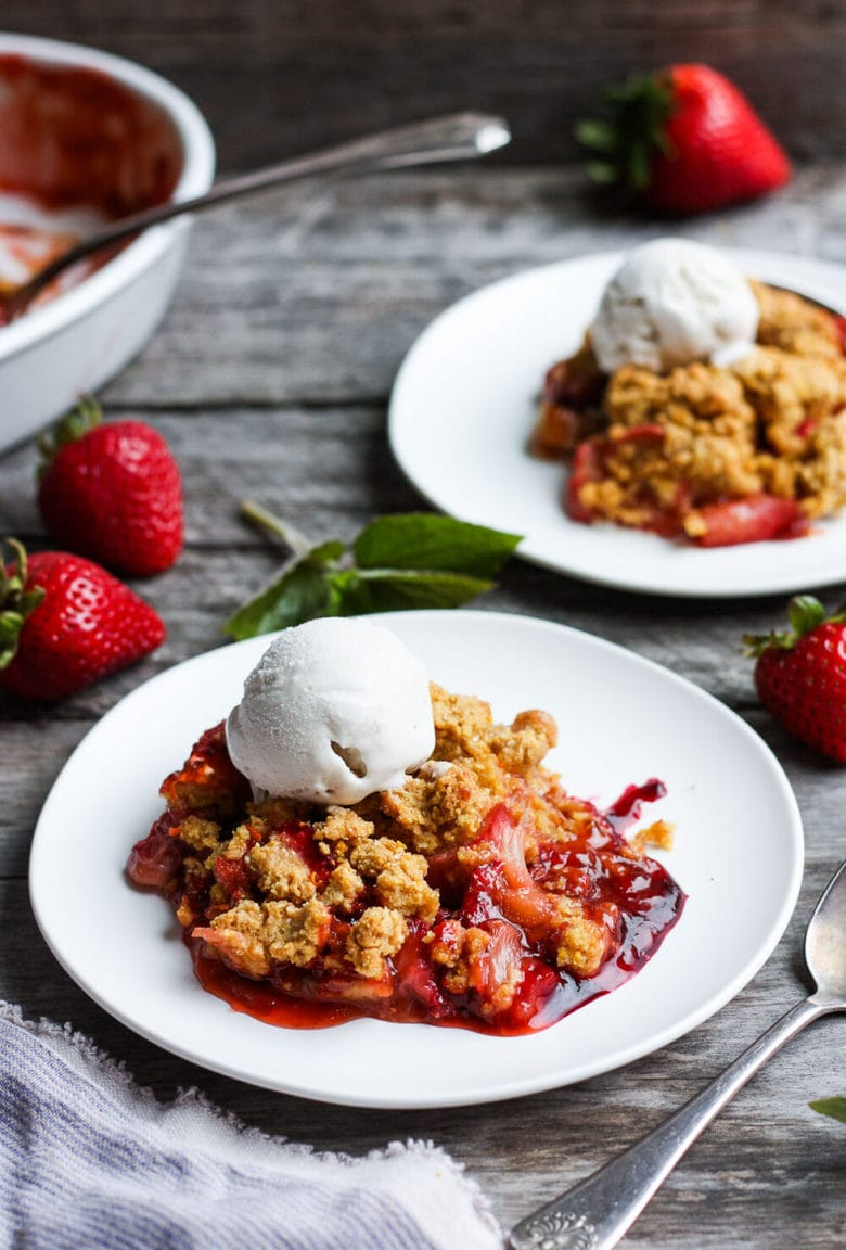 A scrumptious Strawberry Rhubarb Cobbler is infused with ginger and orange zest and topped with a golden corn flour crust. #strawberrycrumble #strawberrycobbler