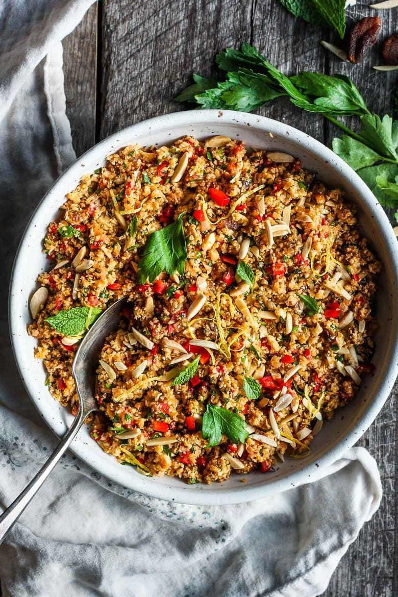 """Moroccan Cauliflower """"Couscous"""" made with riced cauliflower, dried apricots, toasted almonds and fragrant Moroccan spices, tossed with fresh parsley, mint and a lemon honey drizzle.  Gluten-free, healthy and vibrantly flavorful! Vegan-adaptable. #cauliflower #cauliflowerrice #couscous"""