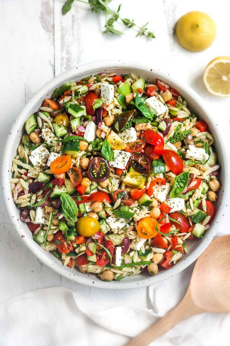 This healthy Greek Pasta Salad is the perfect make-ahead pasta salad for summertime picnics, bbqs, potlucks and easy dinners. A hearty ratio of fresh veggies combined with tender orzo pasta, chickpeas tossed in the tastiest Greek salad dressing.#greekpastasalad