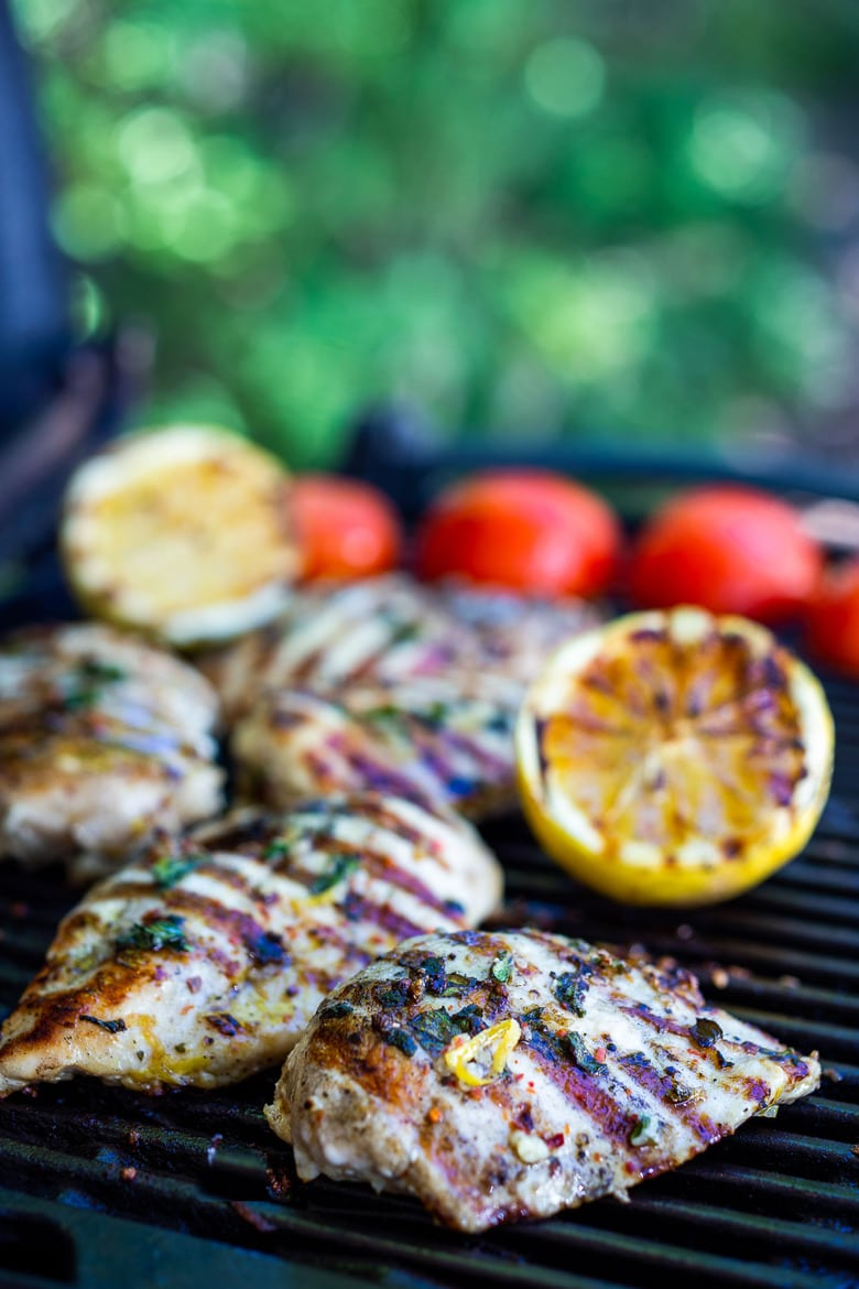 Grilling lemon herb chicken breast on a grill with grilled lemons