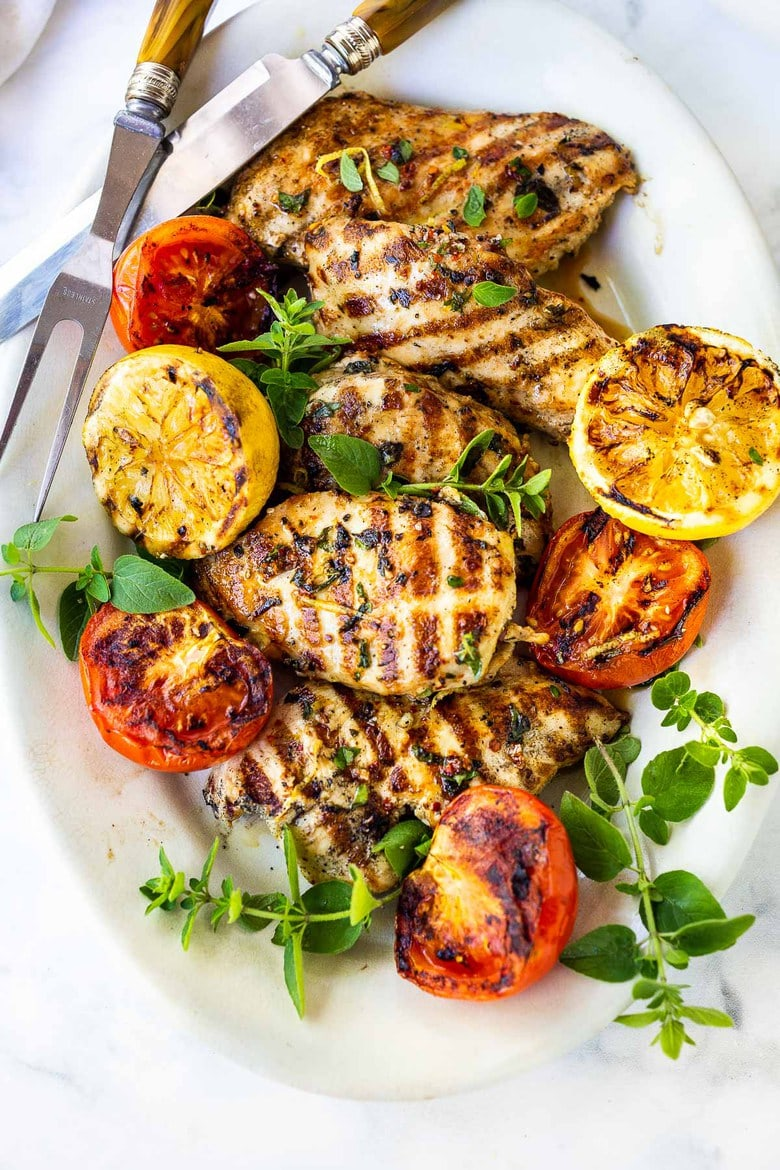 A simple, easy recipe for the juiciest, most flavorful Grilled Lemon Herb Chicken with grilled lemons, that turns out perfect every time. Make this with skinless chicken breast or chicken thighs to pair with salads or veggies.#grilledchickenbreast #grilledchicken
