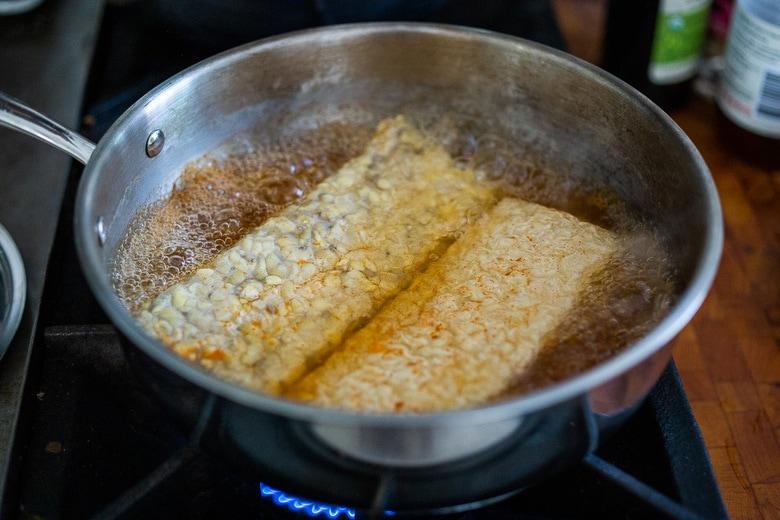 tempeh simmering in a pan.