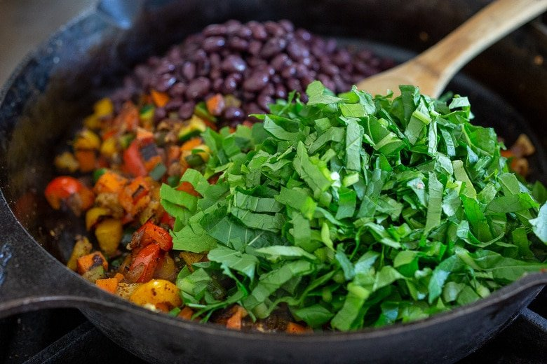 greens and blackbeans being added to the veggies in a pan