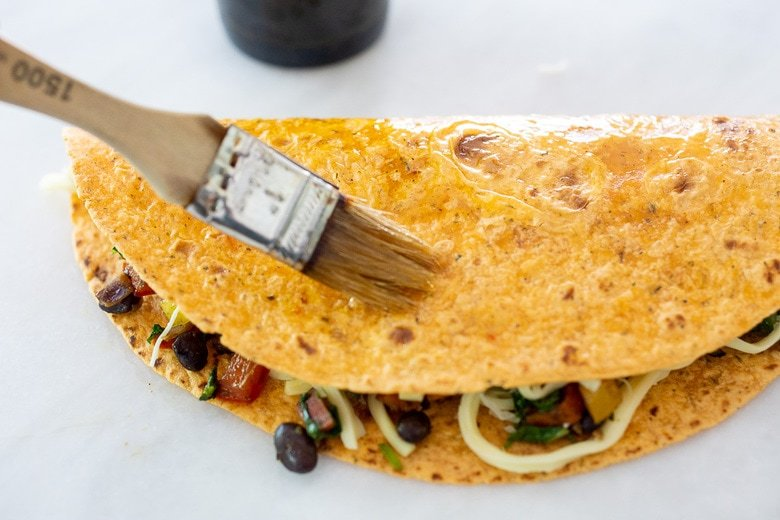 folded and filled tortilla being brushed with olive oil.