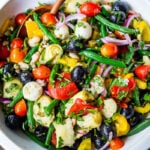 Antipasto Salad with white beans, aritchoke hearts, olives, fresh veggies, and lots of herbs, tossed in a simple Italian dressing. Vegan and Low Carb adaptable!