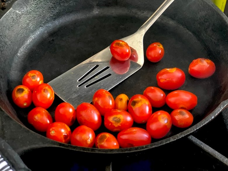 tomatoes being charred in a cast iron skillet