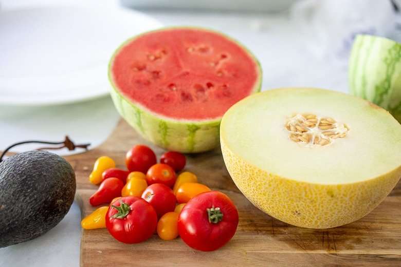 tomatoes and melons on a cutting board