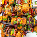 Grilled Veggie Kabobs with your choice of protein (tempeh, tofu, chicken, or shrimp) loaded up with healthy summer veggies and a flavorful harissa yogurt sauce. Vegan adaptable!