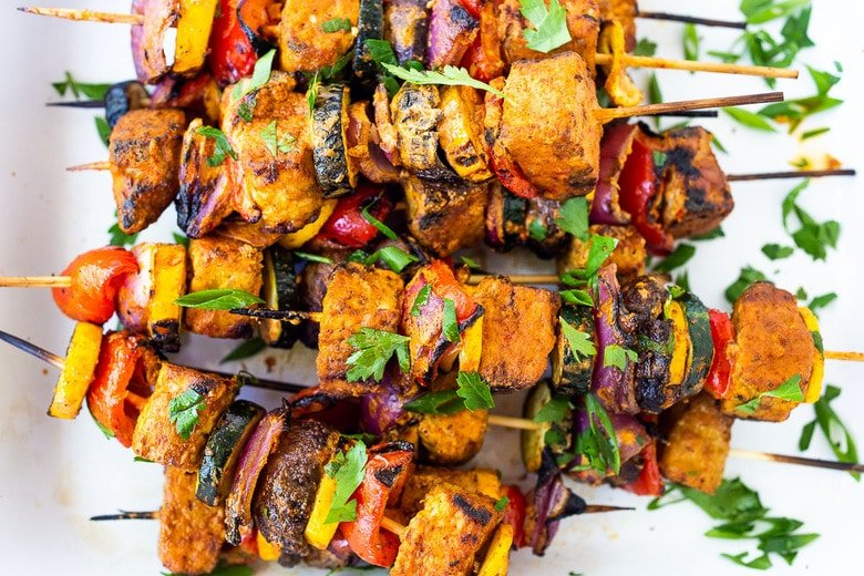 grilled veggie kabobs with harissa yogurt on a platter, scattered with fresh herbs