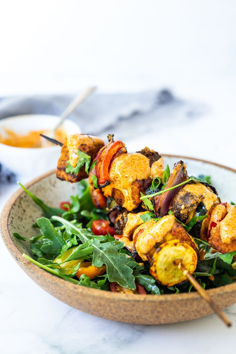 Grilled Veggie Kabobs with Harissa Yogurt -made with your choice of protein (tempeh, tofu,or chicken)! A delcious summer meal that packs a big punch of flavor! Perfect for summer bbqs and gatherings! Served over greens in a bowl.