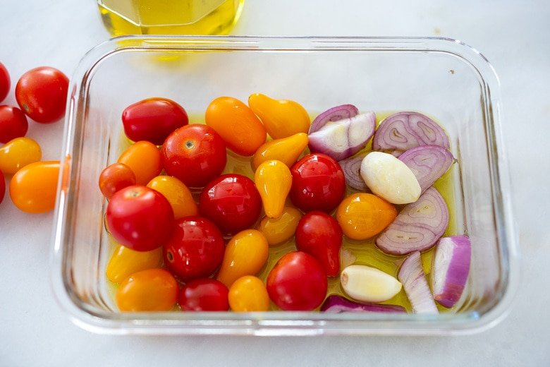 tomatoes, garlic and shallot in a glass roasting pan